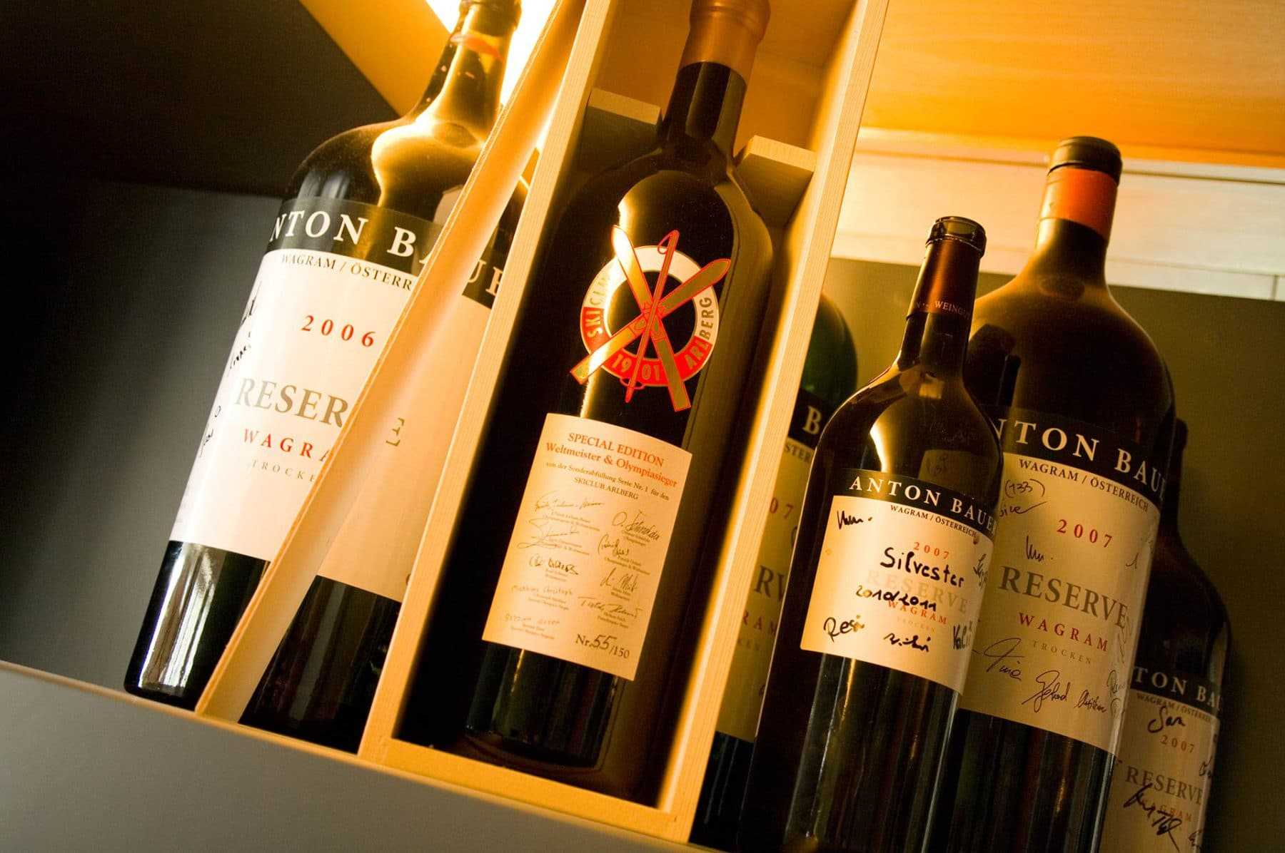 A few selections of the Restaurant's fine wines, all well lit with one bottle inside of a wooden box.