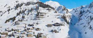 Stuben Dorf mit schoenen verschneiten Bergen und Sonnenschein
