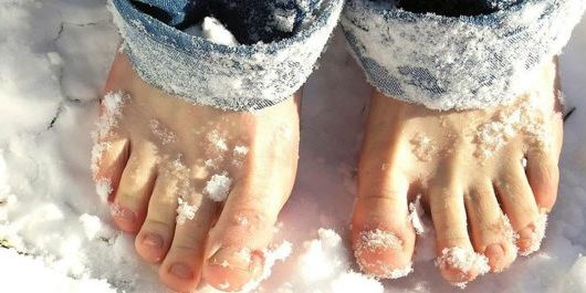 Close up of bare comfy feet in the snow