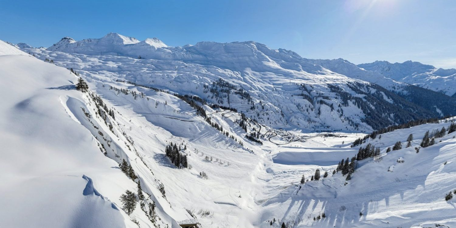 Panormaic snow filled winter scene showing the Village of Stuben in the distance with sun shining above.
